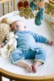 Het oude geluid van zeven maanden van de babyjongen in slaap in zijn voederbak Stock Afbeelding