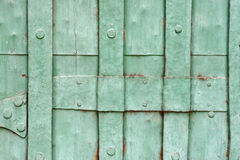 Het oude groene geschilderde vastgenagelde detail van de metaaldeur Stock Afbeeldingen