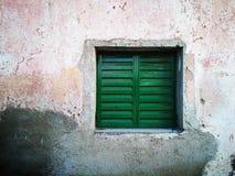 Het oude groene venster van het bladmetaal in een versleten muur royalty-vrije stock foto
