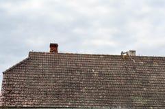 Het oude oude hellende driehoekige die dak van het huis, het plattelandshuisje is vuil met slagtanden met mos tegen de blauwe hem royalty-vrije stock afbeelding