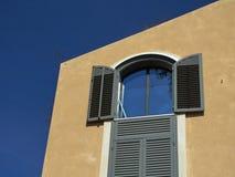 Het oude huis, geschilderde geel, in de vensters van het open venster de blauwe hemel, Jeruzalem, wordt Israël weerspiegeld Stock Foto