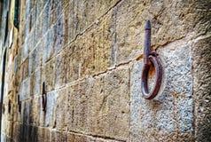 Het oude ijzerhoepel hangen op steenmuur stock afbeelding