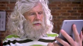 Het oude Kaukasische mannetje met ontzagwekkende witte baard en lang omvangrijk haar typt op zijn tablet in modern baksteenbureau stock video