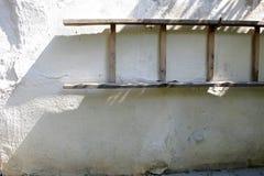 Het oude ladder hangen op witte muur van rustiek coun tryhouse met schaduw stock afbeeldingen