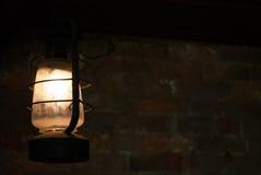 Het oude lamp hangen in donkere ruimte met erachter bakstenen muur Royalty-vrije Stock Foto's