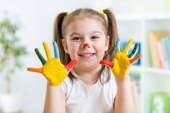 Het oude meisje van vijf jaar met handen schilderde in kleurrijk Royalty-vrije Stock Foto