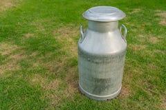 Het oude metaal kan op melk op groene werf Royalty-vrije Stock Afbeeldingen