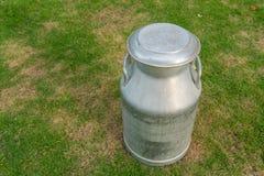 Het oude metaal kan op melk op groene werf Stock Foto's