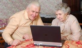 Het oude paar kijkt aan laptop met actieve rente Stock Afbeeldingen