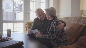 Het oude paar zit in de bank, lettend op oude foto's Man de knuffelvrouw en bekijkt haar met liefde en hartstocht amazing stock videobeelden