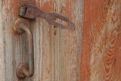 Het oude roestige deurhandvat en een ijzer sluiten in de roest op de houten deuren stock foto's