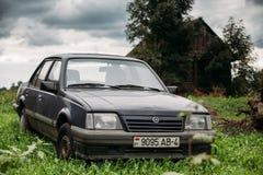 Het oude roestige parkeren van Opel Ascona C van de sedanauto in groen gras op oud Royalty-vrije Stock Afbeeldingen