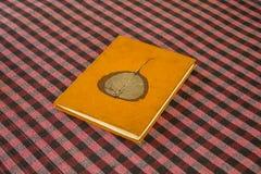 Het oude sjofele heldere oranje boek met een grijs droog blad op de dekking ligt op een vage geruite rode witte zwarte tafelkleed stock foto