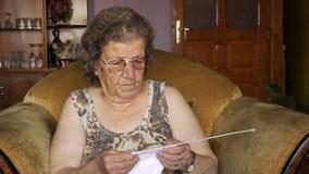 Het oude teruggetrokken vrouw breien in huis stock videobeelden