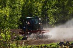 Het oude tractor ploegen bij zonsondergang Stock Foto
