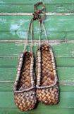 Het oude traditionele Russische schoeisel van bastschoenen op een groene muur Stock Fotografie