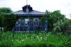 Het oude verlaten blokhuis met een tuin stock afbeelding