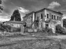 Het oude verlaten helft-geruïneerde huis met uitgebroken Stock Afbeelding