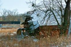 Het oude vernietigde huis, het gebroken doen ineenstorten dak van het huis, het verlaten huis, de muren en het dak van het huis w Stock Foto