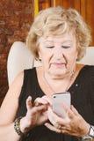 Het oude vrouw typen op telefoon stock foto