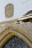 Het oude wapenschild over de poort van het kasteel Stock Foto