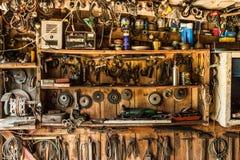 Het oude werkende hulpmiddel op de achtergrond van houten panelen, de hulpmiddelen van artisanaal hangt op spijkers stock fotografie