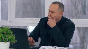 Het oude zakenmanwerk met laptop computer en neemt nota's in notitieboekje in bureau