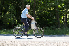 Het oudere mannetje op een fiets vervoerden de metaal-container melkachtig in Bartne royalty-vrije stock fotografie