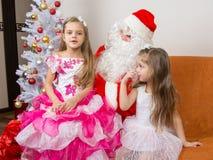 Het oudere meisje zit op overlapping van Santa Claus en vertelt gedicht stock afbeeldingen