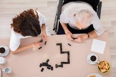 Het oudere Spel van de Vrouwen Speeldomino met Haar Verpleegster Royalty-vrije Stock Fotografie