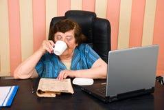 Het oudere uitvoerende lezingsnieuws en drinkt koffie Royalty-vrije Stock Afbeeldingen