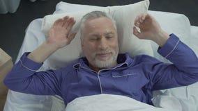 Het oudere zonnebaden in zijn bed die zich bij nieuwe orthopedische matras, comfortabele slaap verheugen stock videobeelden