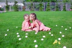 Het oudere zuster kussen jonger op een groen gras van Stock Fotografie