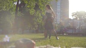 Het oudere zuster spelen met jongere broer in het de zomerpark Vrije tijd in openlucht Vriendschappelijke relaties tussen sibling stock video