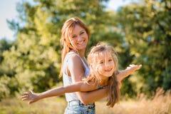 Het oudere zuster spelen in openlucht met jonger op zonnige dag Royalty-vrije Stock Foto