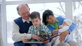Het ouderschap, gepensioneerdefamilie met kinderen brengt vrije tijd met boek door stock video
