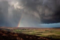 Het overgaan van onweersbui met hagel en een regenboog stock afbeelding