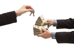 Het overhandigen Duizenden Dollars voor Huissleutels op Wit Royalty-vrije Stock Foto