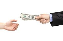Het overhandigen van de hand geld aan een andere hand Stock Afbeeldingen