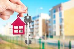Het overhandigen van sleutels op de huisachtergrond Royalty-vrije Stock Foto
