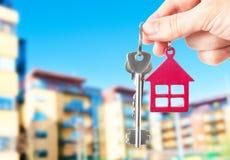 Het overhandigen van sleutels op de huisachtergrond Stock Afbeelding