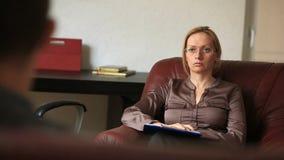 Het overleg met een psycholoog, een vrouwelijke therapeut raadpleegt een patiënt een mens met een bezorgdheidswanorde stock footage