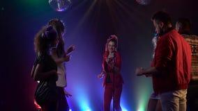 Het overlegmeisje van de club zingt retro muziek rond mensen het dansen Rook achtergrond Langzame Motie stock video