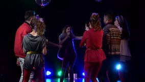 Het overlegmeisje van de club zingt retro muziek rond mensen het dansen Rook achtergrond Langzame Motie stock videobeelden