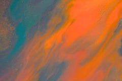 Het overlopen van heldere oranje en donkerblauwe verf op papier Stock Afbeeldingen