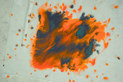 Het overlopen van heldere oranje en donkerblauwe verf op papier Stock Fotografie