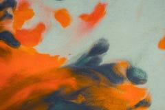Het overlopen van heldere oranje en donkerblauwe verf op papier Royalty-vrije Stock Foto's
