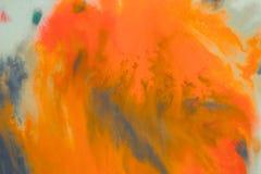 Het overlopen van heldere oranje en donkerblauwe verf op papier Stock Foto's