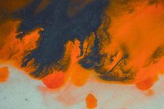 Het overlopen van heldere oranje en donkerblauwe verf op papier Royalty-vrije Stock Foto