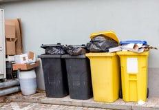 Het overlopen van plastic afvalblikken met vuilniszakken, kartondozen en een container met een vloeistof stock foto